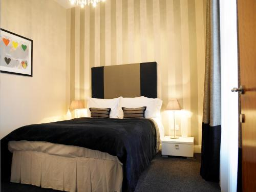 A bed or beds in a room at Kensington House Aparthotel